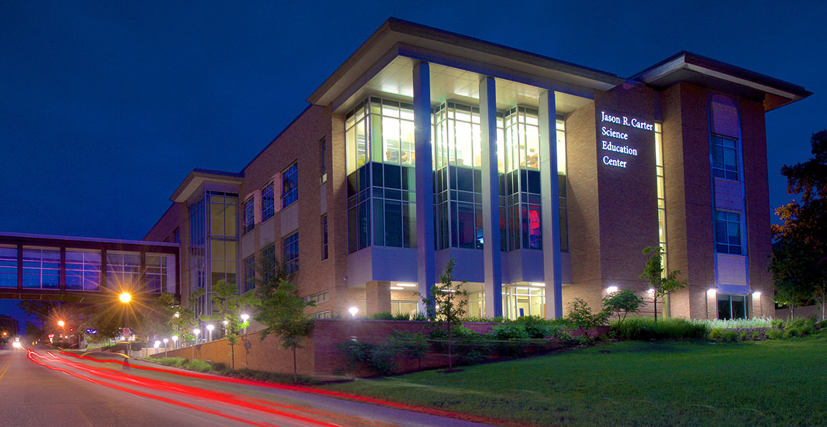 Evening photograph of Metropolitan State University's Jason R. Carter Science Education Center located on the Saint Paul Campus. Evening sky is dark blue with building light shining bright and remnants of taillights appearing as red streaks from cars driving by on East Sixth Street, West to East.