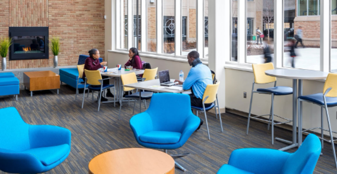 Photograph in Metropolitan State University's Student Center where two female students are eating their lunches and a male student studying at the next table, with a gas fireplace within a brick wall burning a low flame in an otherwise decorated room with bright blue cushioned chairs, yellow backed and dark blue table chairs, and large windows where passersby can be seen walking towards campus and into the parking ramp.