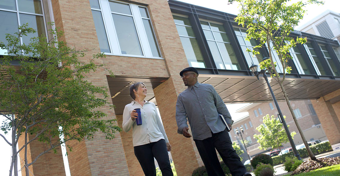 Photograph of an African American male and a Caucasian female smiling, walking and talking on the grounds of Metropolitan State University's library and learning center with the skyway shown that connects the library to the other building on the Saint Paul campus.