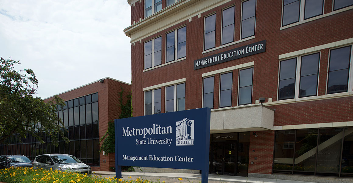 "Photograph of Metropolitan State University's Management Education Center located in Minneapolis, Minnesota; red brick building with white trim, blue sign within an elevated bed of yellow lilies across the street but in front of the building stating, in white lettering, ""Management Education Center"" with Metropolitan State's logo shown in white."