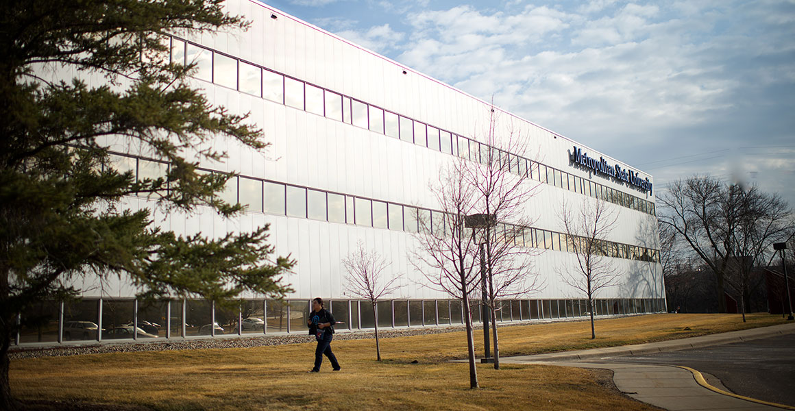 Photograph of the West side of Metropolitan State University's Midway Center in the very early Spring, with yellow grass and bare trees; a man walks on the sidewalk toward the building from the parking lot.