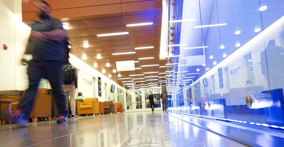 Photograph of students walking in a well-lit corridor at one of Metropolitan State University's locations; bright lights, reflects, and the blur of a student walking past.