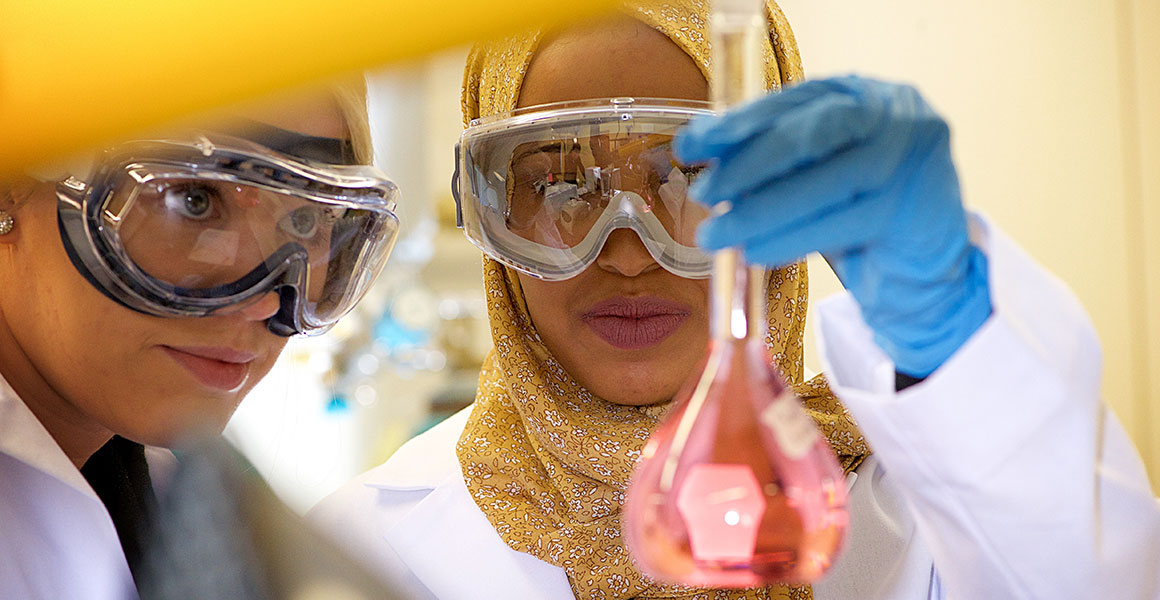 Photograph of two females wearing goggles and white lab coats examining a beaker with pink liquid in in one of the science labs in the Jason R. Carter Science Education Center on Metropolitan State University's Saint Paul location.