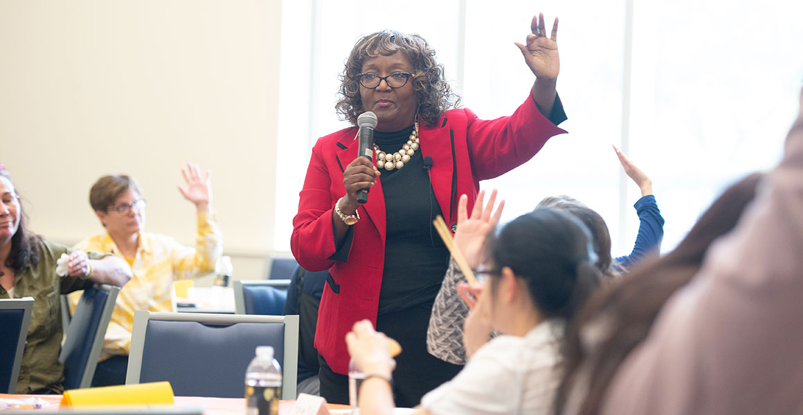 Photograph of an African American instructor, Dr. Denise Williams, leading a group of students in a day lecture class or workshop.