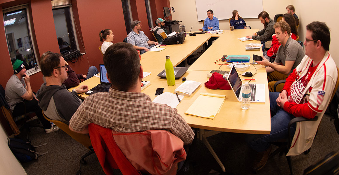Photograph of students gathered around large tables in a smaller meeting room using laptops or taking notes as they enjoy a discussion with the professor in a more non-traditional environment at one of Metropolitan State University's teaching locations.