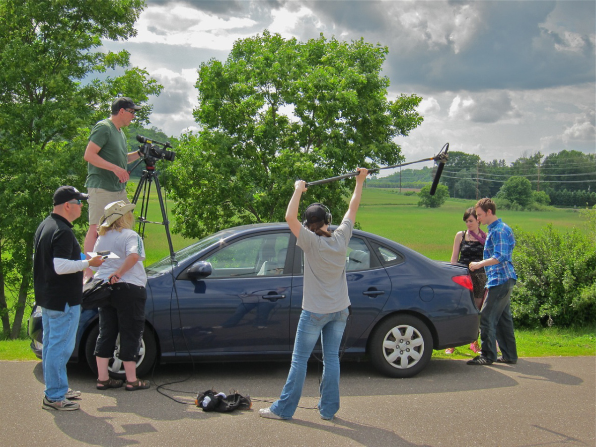 Byrne often works with students and alumni. Pictured here are some of the crew at a wayside rest somewhere in Wisconsin filming the last scene of Madison. Metropolitan State University alumni who worked on the film include Joy LaDuke, Jill Schmaedeke, Zach Jansen and David Lee. The film stars Catherine Johnson Justice and Billy Mullaney, pictured on the right. James Byrne is filming on the car hood. Right after this picture was taken the windshield shattered.