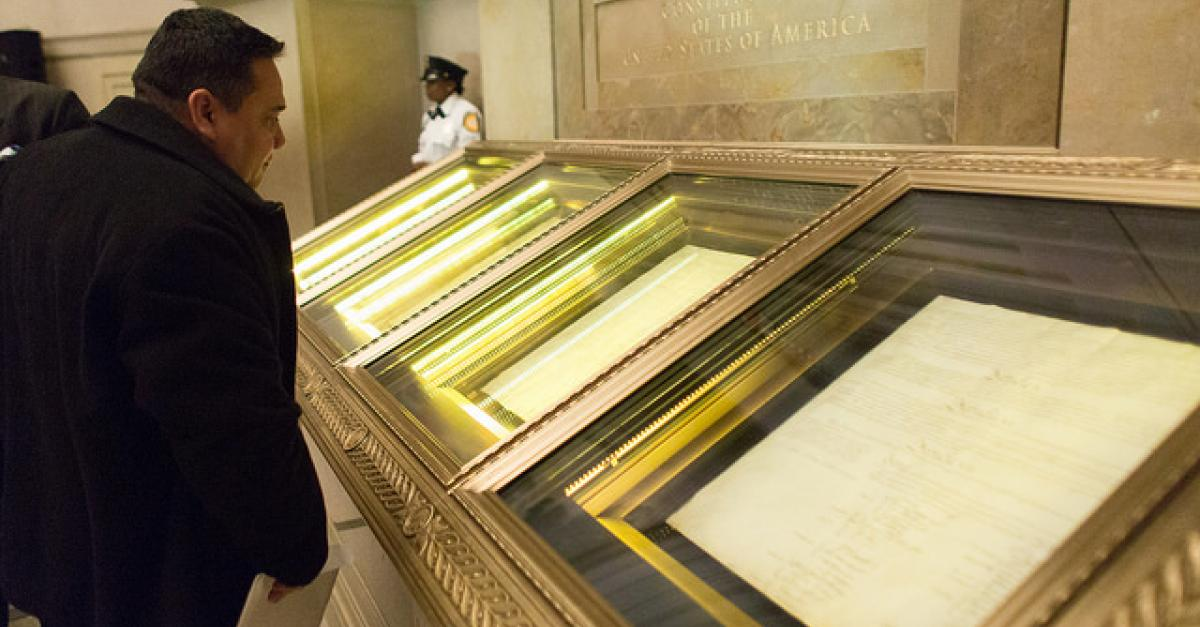 Man looking at historic copies of U.S. Constitution