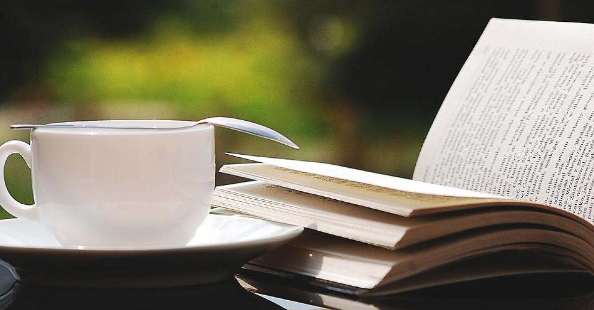 A coffee cup next to an open book