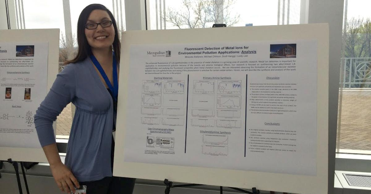 Woman displays her work at the Student Poster Conference presentation