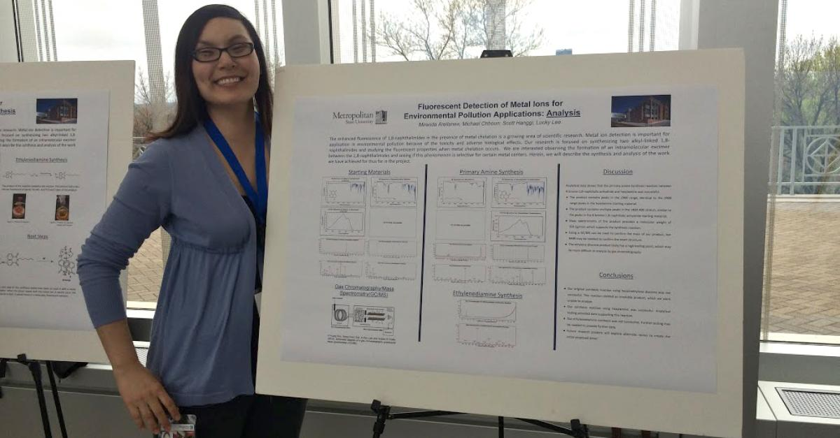 Woman displays her work at the Student Poster Conference