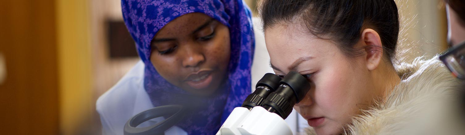 A woman looks through a microscope; another student stands next to her.