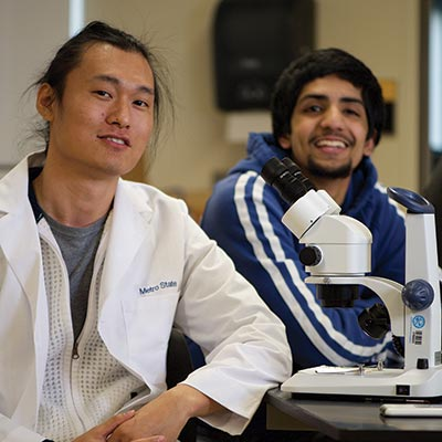 Two men, one wearing a Metro State lab jacket, smile at the camera while sitting in front of a microscope in a classroom lab.