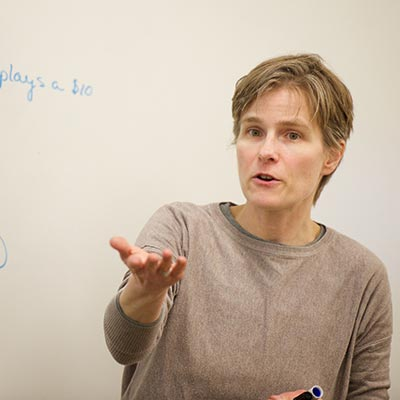 A woman lectures to a class in front of a dry-erase board.
